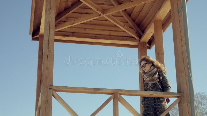 Zekere mooie bedrijfsvrouw die in de houten de reddingstoren van A op het strand tijdens de afwezigheid van sesosis lopen royalty-vrije stock afbeeldingen