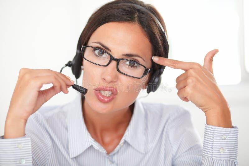 Zekere mooie vrouw die op hoofdtelefoon converseren stock foto