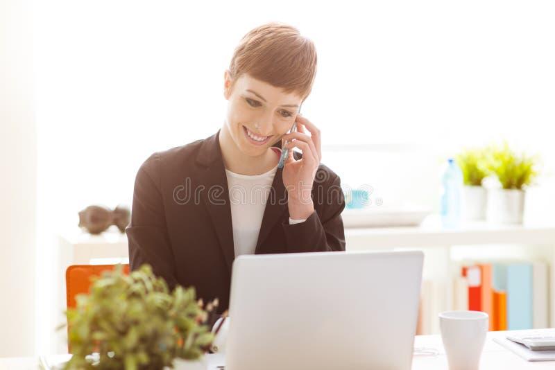 Zekere onderneemster die een slimme telefoon met behulp van royalty-vrije stock foto's