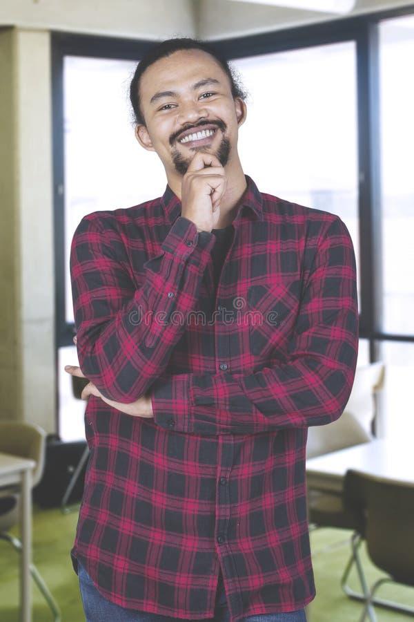 Zekere ontwerperstudent die in een klaslokaal glimlachen stock fotografie