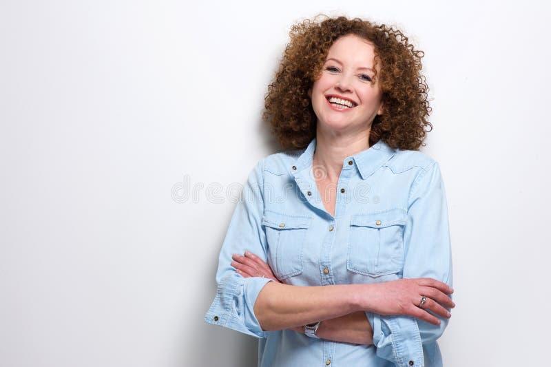 Zekere oudere vrouw die met gekruiste wapens glimlachen stock foto's