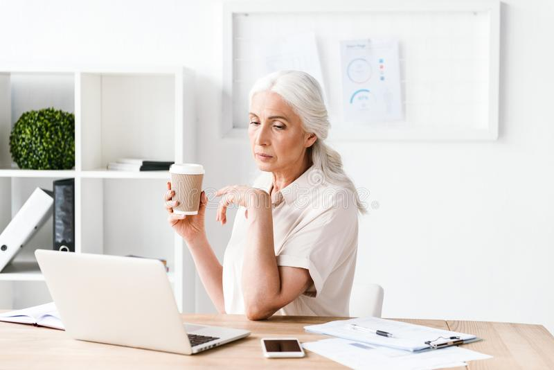 Zekere rijpe bedrijfsvrouw die aan laptop werken stock afbeelding