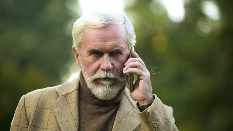Zekere rijpe mens die op telefoon spreken, die aan tegenstander, mededeling luisteren royalty-vrije stock foto