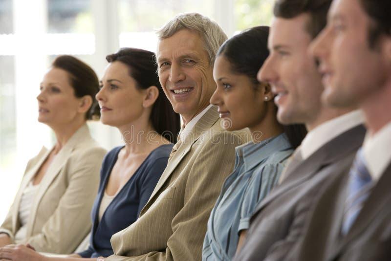 Zekere rijpe zakenman met team royalty-vrije stock afbeelding