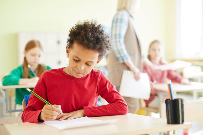 Zekere schooljongen die antwoorden in spatie merken stock afbeeldingen