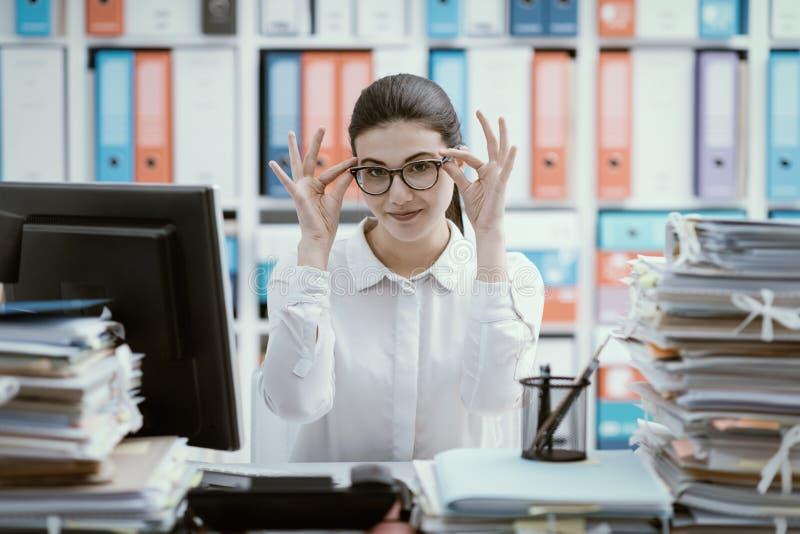 Zekere secretaresse die haar glazen aanpassen royalty-vrije stock foto's