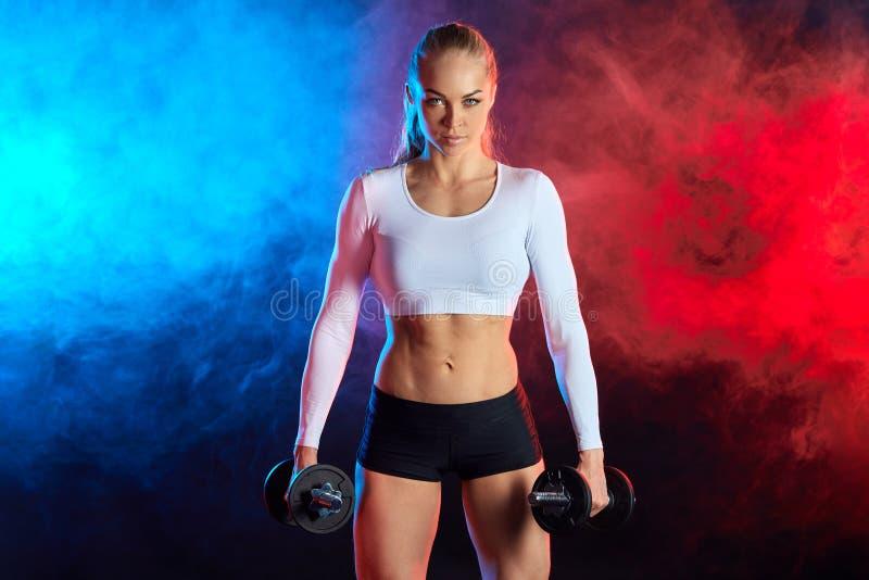 Zekere sexy vrouw in sportieve kleren die omhoog spieren pompen stock foto
