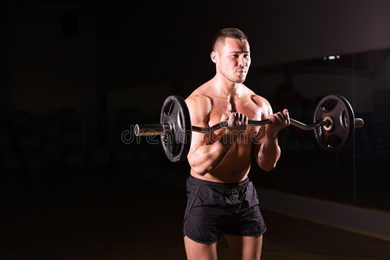 Zekere spiermens opleiding met barbell Close-upportret van professionele bodybuildertraining met barbell bij gymnastiek stock afbeeldingen