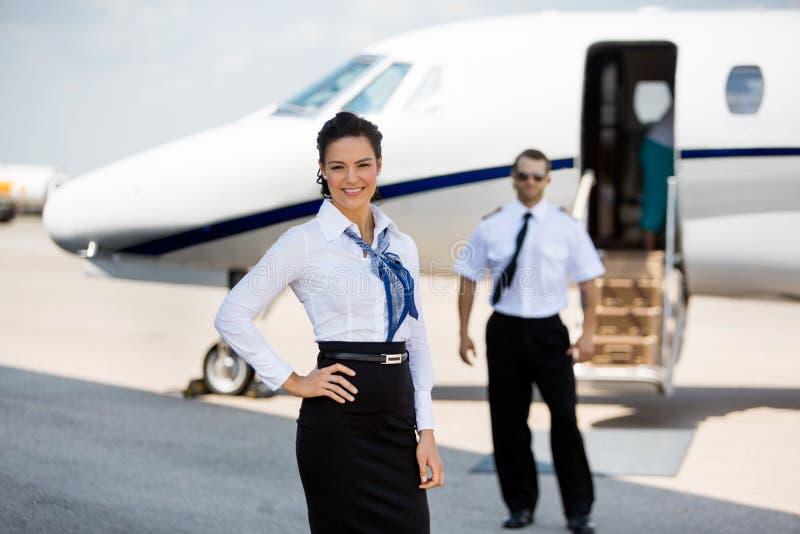 Zekere Stewardessen die met ProefAnd glimlachen stock afbeeldingen