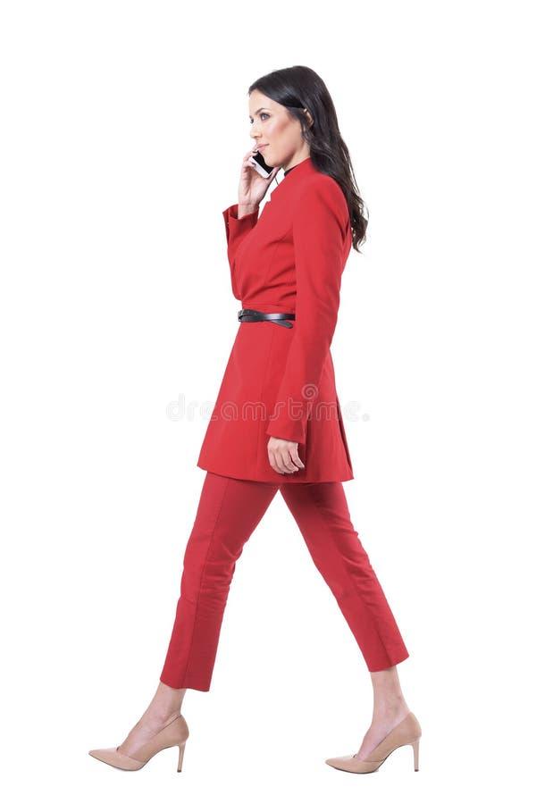 Zekere succesvolle bedrijfsvrouw die en op de telefoon lopen spreken die weg eruit zien royalty-vrije stock foto's