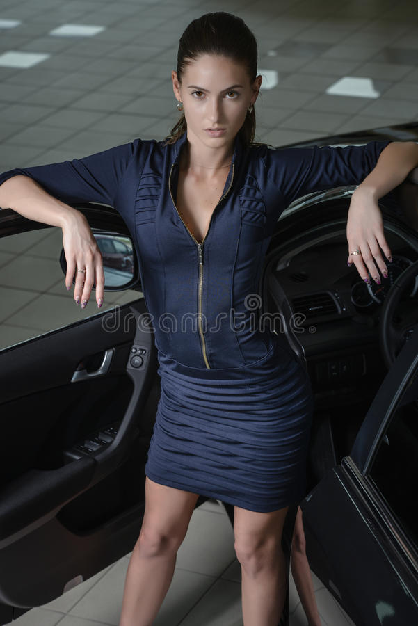 Zekere vrouw die en haar ellebogen bevinden leunen zich aan een open autodeur royalty-vrije stock afbeelding