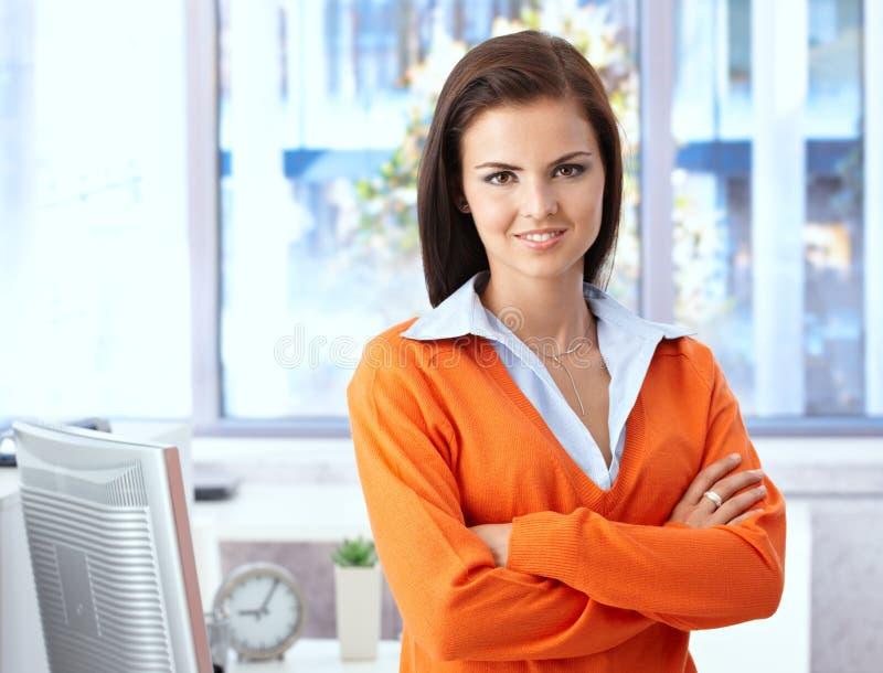 Zekere vrouw die in helder bureau glimlacht royalty-vrije stock fotografie
