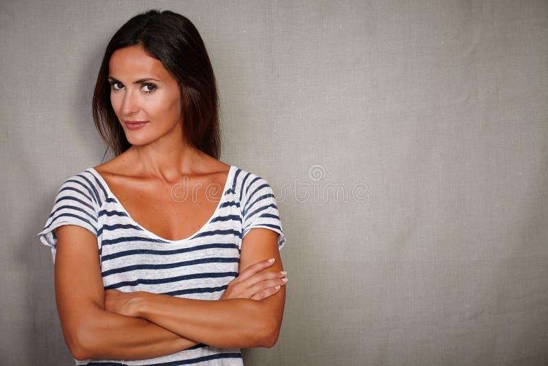 Zekere vrouw die zich met gekruiste wapens bevindt stock afbeelding
