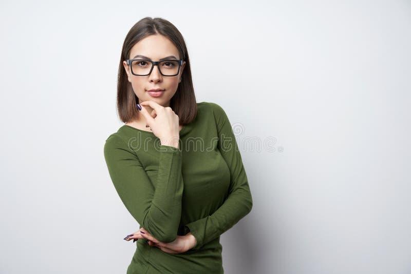 Zekere vrouw in glazen met hand op kin stock afbeeldingen