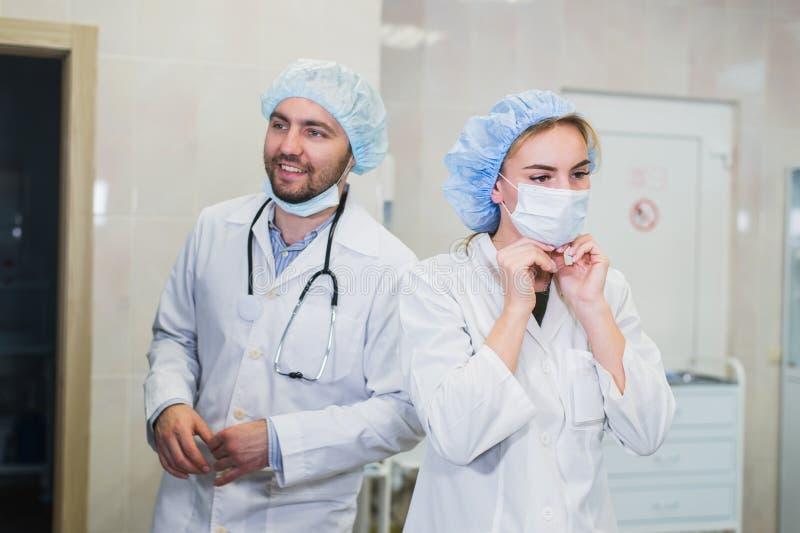 Zekere vrouwelijke arts die op medisch gezichtsmasker zetten terwijl het voorbereidingen treffen voor verrichting, haar mannelijk stock fotografie