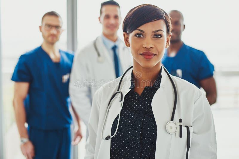 Zekere vrouwelijke arts voor team royalty-vrije stock afbeelding