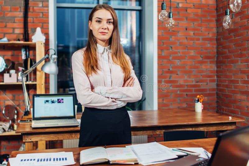 Zekere vrouwelijke bedrijfseigenaar die zich bij haar het werkbureau bevinden die wapens vouwen die camera in creatieve ontwerpst stock afbeeldingen