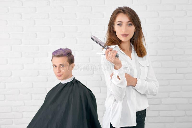 Zekere vrouwelijke kapper die camera bekijken die zich voor cliënt bevinden stock afbeelding