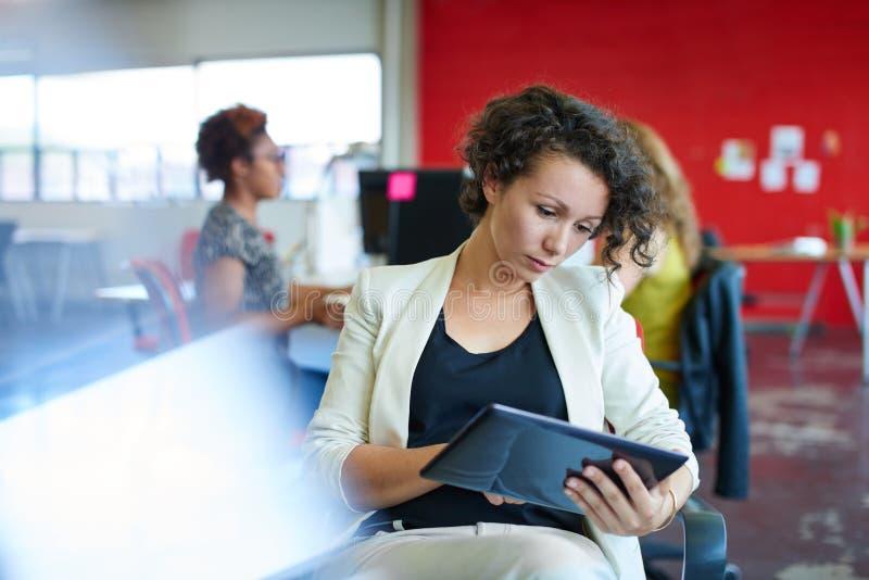 Zekere vrouwelijke ontwerper die aan een digitale tablet in rode creatieve bureauruimte werken royalty-vrije stock foto