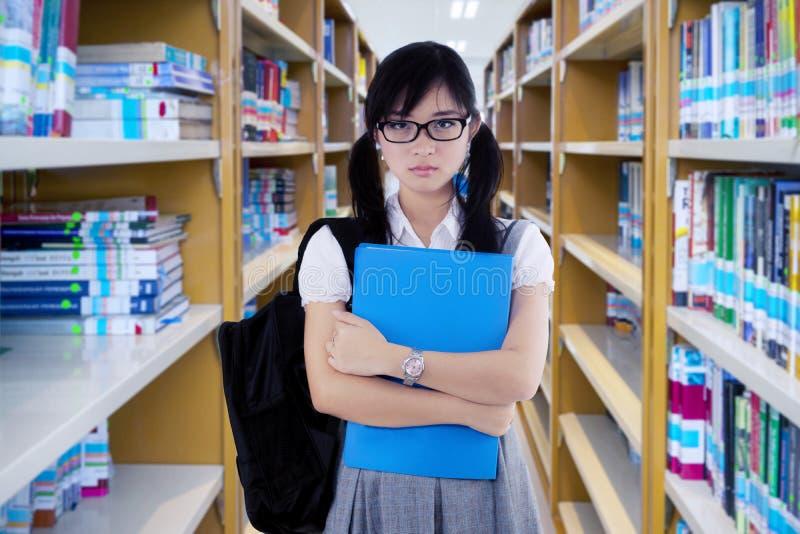Zekere vrouwelijke student die zich in de bibliotheek bevinden stock afbeelding