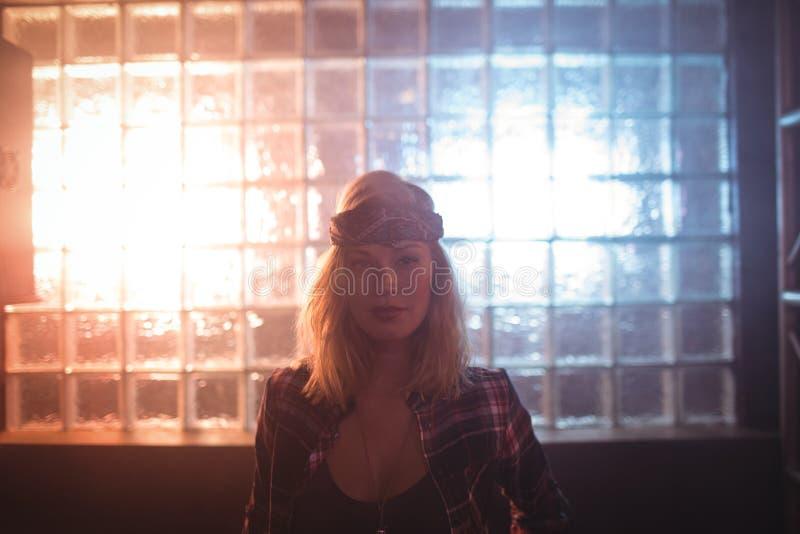 Zekere vrouwelijke zanger die zich tegen venster in nachtclub bevinden royalty-vrije stock afbeelding