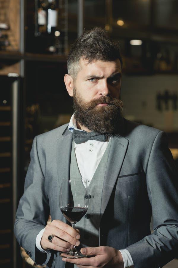 Zekere winemaker in romantische atmosfeer van sigarenclub sigarenclub, ernstige winemaker met glas in pak royalty-vrije stock afbeelding