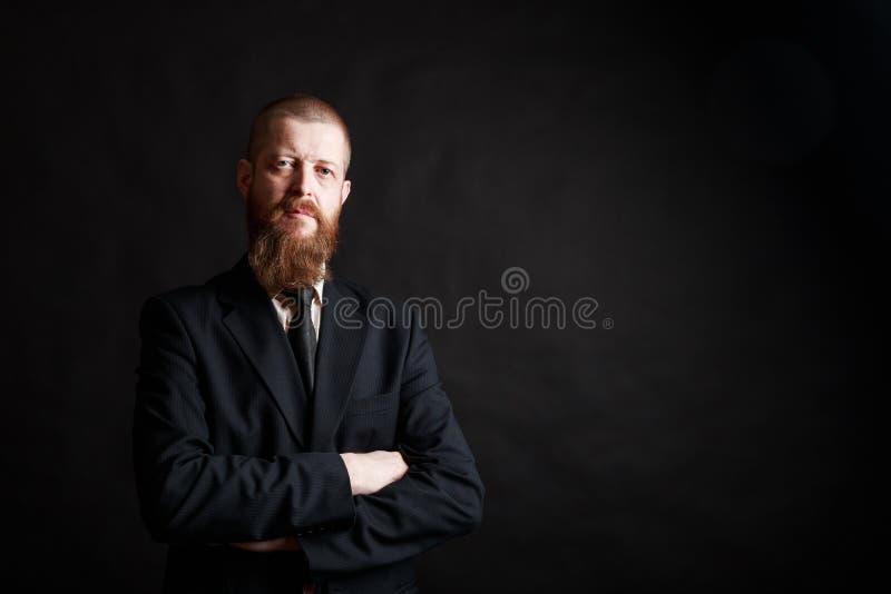 Zekere zakenman De zekere midden-leeftijds gebaarde mens in formalwear houdend zijn wapens kruiste en bekijkend camera stock foto