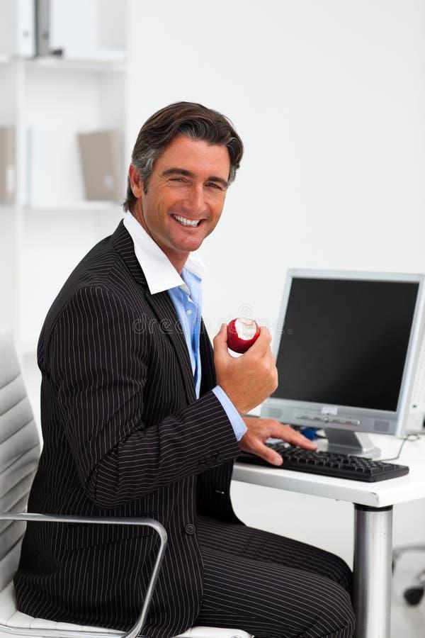 Zekere zakenman die een rode appel eet royalty-vrije stock foto