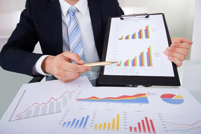 Zekere zakenman die grafieken in bureau tonen stock afbeeldingen