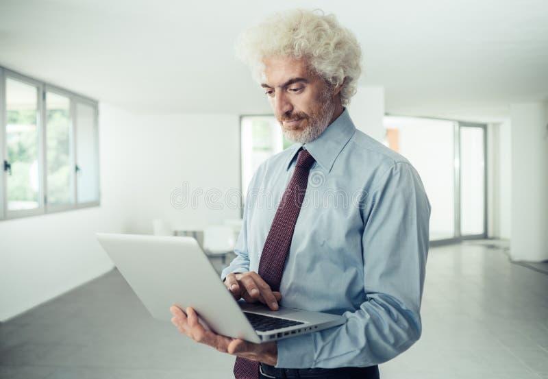 Zekere zakenman die laptop houden stock afbeeldingen
