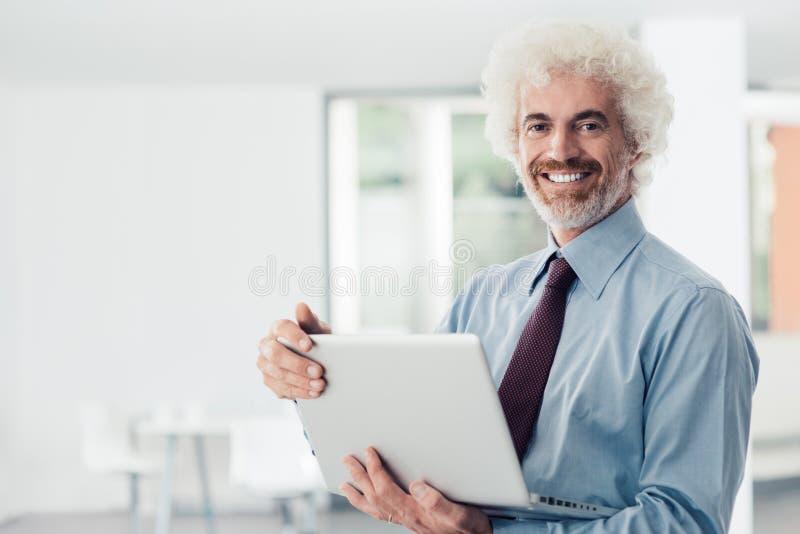 Zekere zakenman die laptop houden stock foto's