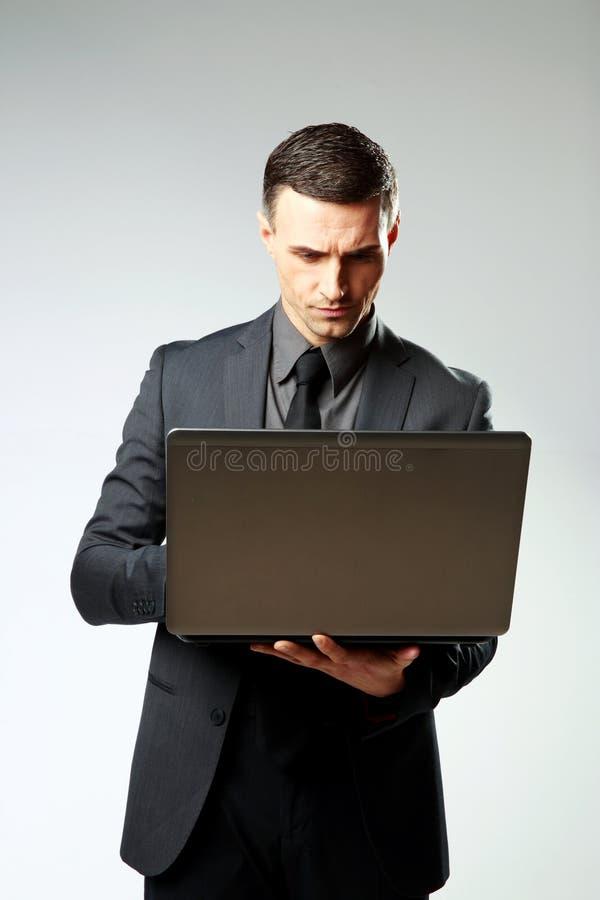 Download Zekere Zakenman Die Laptop Met Behulp Van Stock Foto - Afbeelding bestaande uit volwassen, holding: 39100756