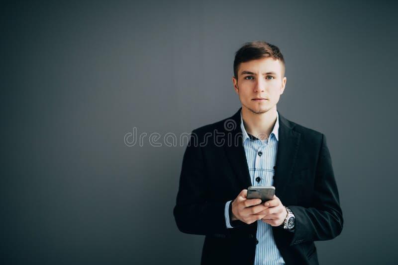 Zekere zakenman die tegen een muur leunen terwijl het gebruiken van smartphone op zwarte achtergrond stock foto