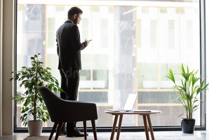 Zekere zakenman die zich dichtbij venster bevinden, die telefoon met behulp van stock afbeeldingen