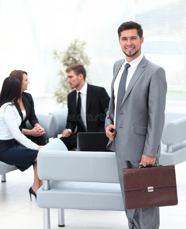 Zekere zakenman met aktentas die zich in de hal van het bureau bevinden stock foto