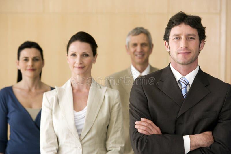 Zekere zakenman met team dat voorbij hem loopt stock fotografie