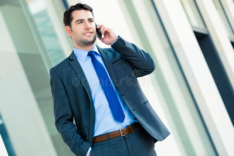 Zekere zakenman openlucht gebruikende telefoon royalty-vrije stock afbeelding
