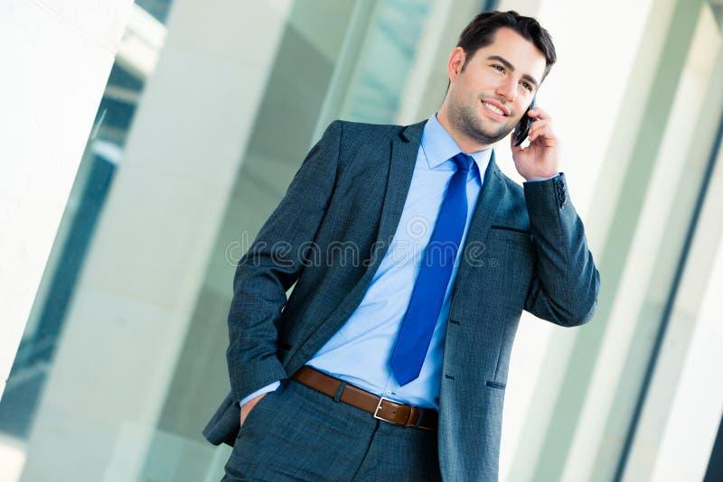 Zekere zakenman openlucht gebruikende telefoon stock afbeelding