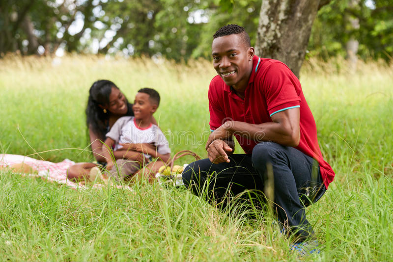 Zekere Zwarte Mens bij Camera glimlachen en Familie die Picknick doen royalty-vrije stock afbeeldingen