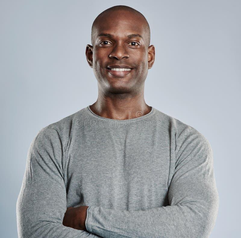 Zekere zwarte mens met prettige glimlach in grijs stock foto