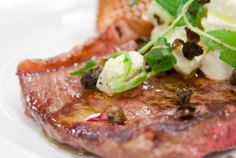 Zeldzaam gekookt lapje vlees met kappertjes en kaasbovenste laagje royalty-vrije stock afbeeldingen