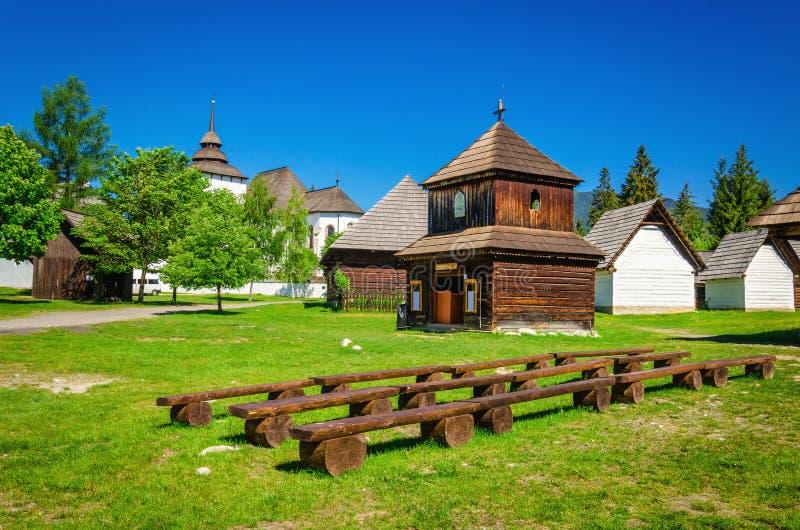 Zeldzame houten klokketoren met volkshuizen Slowakije stock fotografie