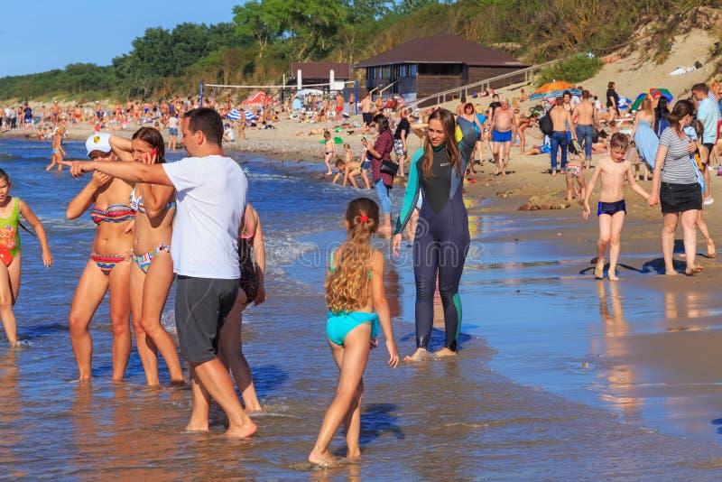 ZELENOGRADSK, ОБЛАСТЬ КАЛИНИНГРАДА, РОССИЯ - 29-ОЕ ИЮЛЯ 2017: Неизвестная молодая женщина в мокрой одежде на пляже песка на Балти стоковые изображения rf
