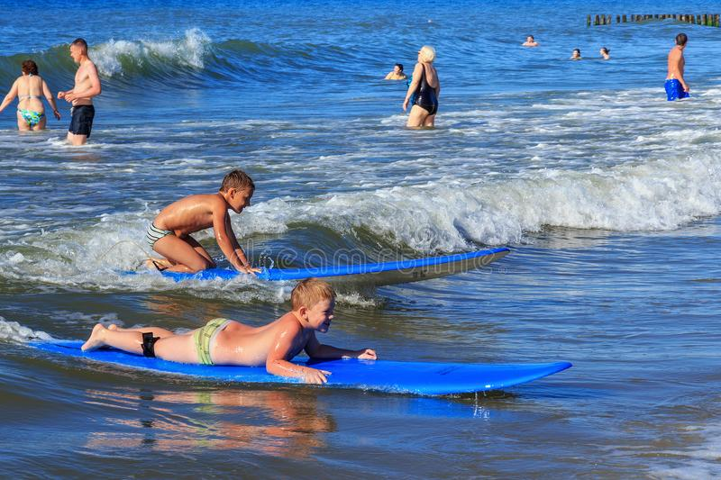 ZELENOGRADSK, KALININGRAD REGION, RUSSIA - JULY 29, 2017: Unknown children with surfboards resting and learning of surfing. stock photos