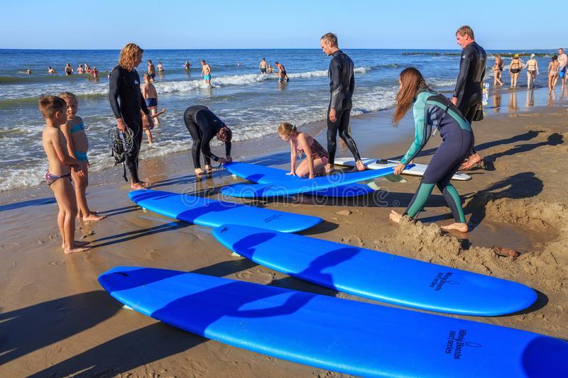 ZELENOGRADSK, KALININGRAD REGION, RUSSIA - JULY 29, 2017: Unknown surfers with surfboards standing on a sandy beach. stock image