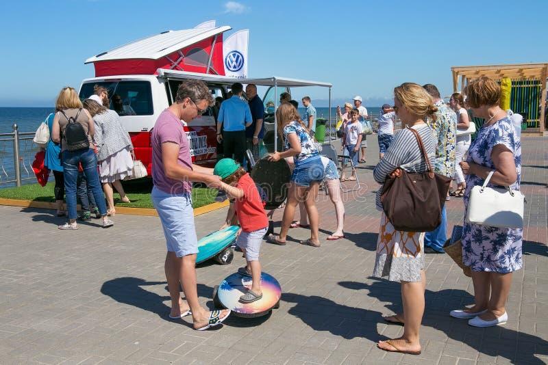 ZELENOGRADSK KALININGRAD REGION, RYSSLAND - JULI 29, 2017: Okända turister near den moderna bilVolkswagen Multivan biltransporten fotografering för bildbyråer