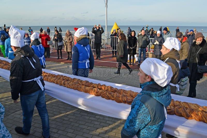 Zelenogradsk, Rússia Os padeiros masculinos carregam a torta doce 18 medidores de comprimento na terraplenagem Festival da torta  fotografia de stock