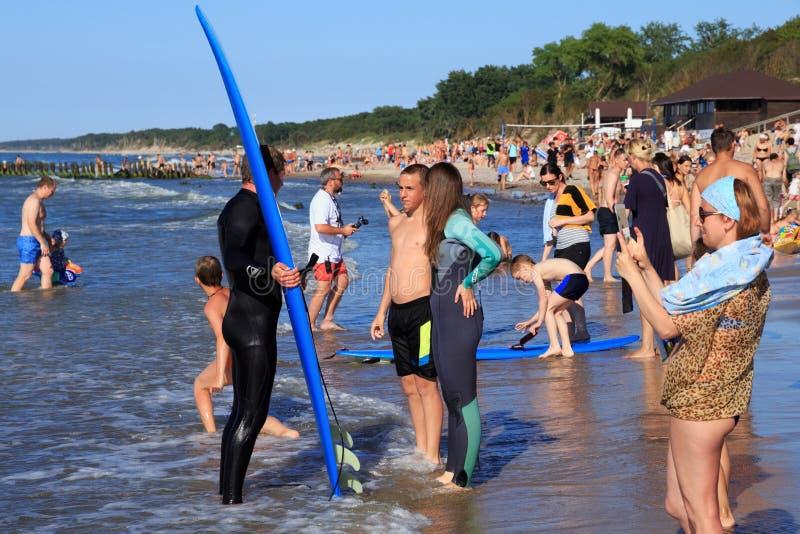 ZELENOGRADSK, REGIÃO DE KALININGRAD, RÚSSIA - 29 DE JULHO DE 2017: Surfistas desconhecidos com a prancha que está em um Sandy Bea imagens de stock royalty free
