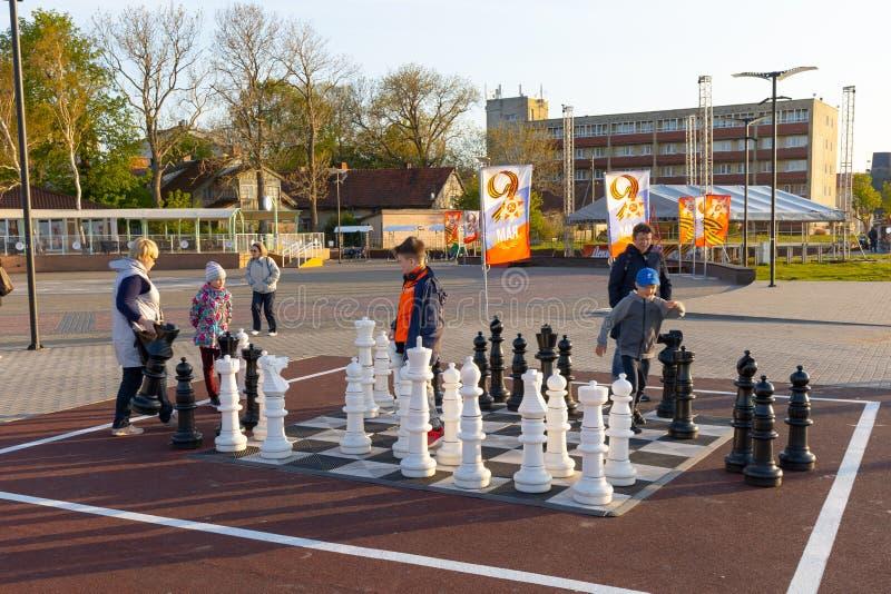 Zelenogradsk, Rusia - 8 de mayo de 2019: Cuadrado del juego de ajedrez en centro de ciudad Muchachos que juegan a ajedrez fotos de archivo