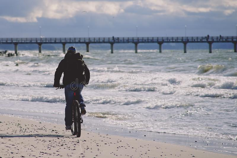 A lone cyclist in dark clothes rides on a sandy beach towards the pier. royalty free stock photo
